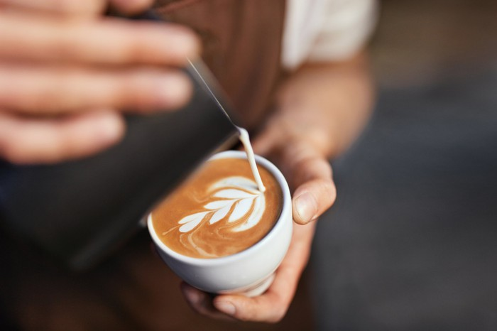 coffee barista pouring cream into cup of coffee