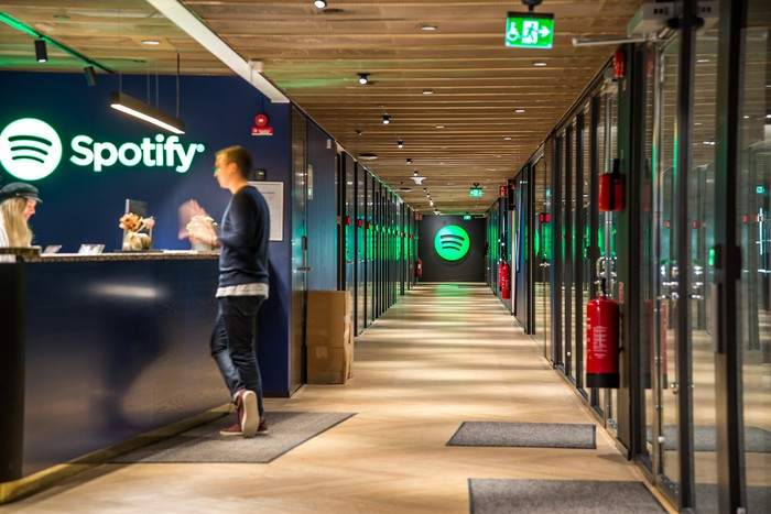 The reception area of an office building with the green Spotify logo at the end of the hallway.