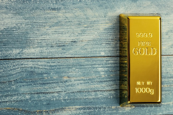 A gold bar on a blue wooden table.
