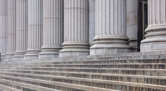 The front steps of a bank with large stone columns out front.