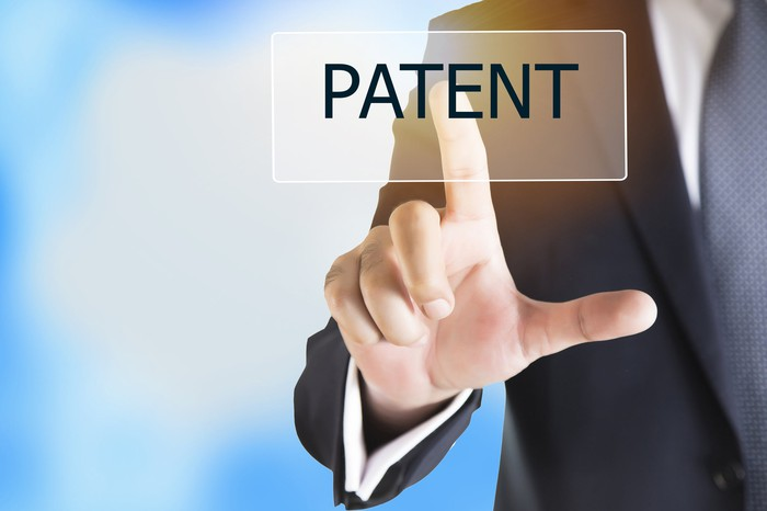 """Businessman's finger pointing to the word """"patent"""""""