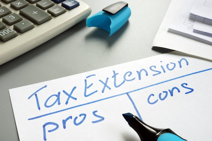 Pen hovering over a paper headed Tax Extension with columns for pros and cons