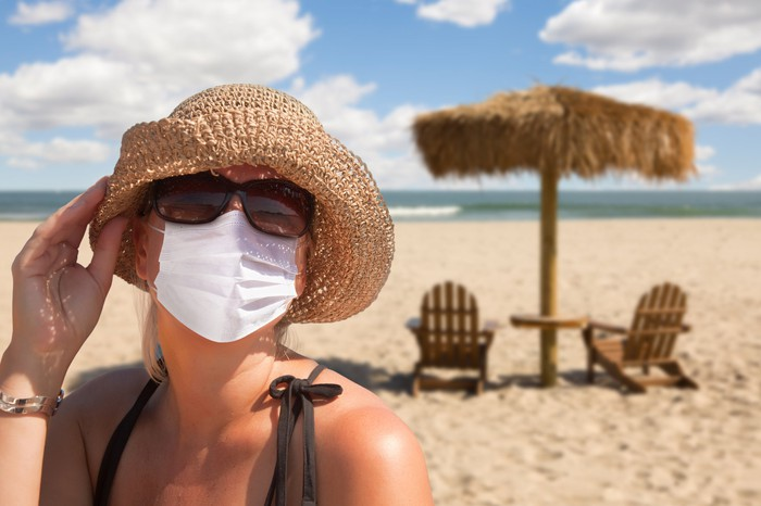 Woman on a beach wearing disposable face mask.
