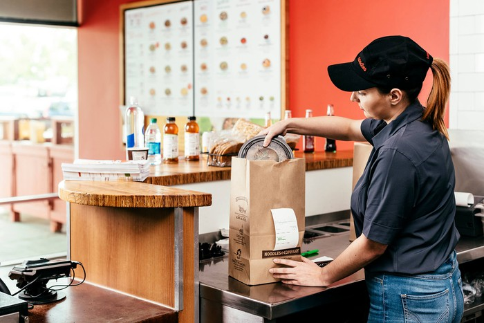 A Noodles & Company employee places food in a bag for a to-go order.