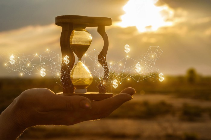 A hand holds an hourglass surrounded by dollar symbols against a sunset background.