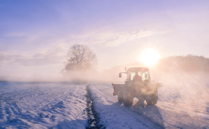 A tractor works in a snow-covered field against a sunrise background.