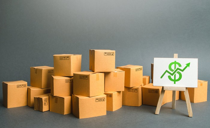 boxes sit on a floor next to an easel with a dollar sign image on it.