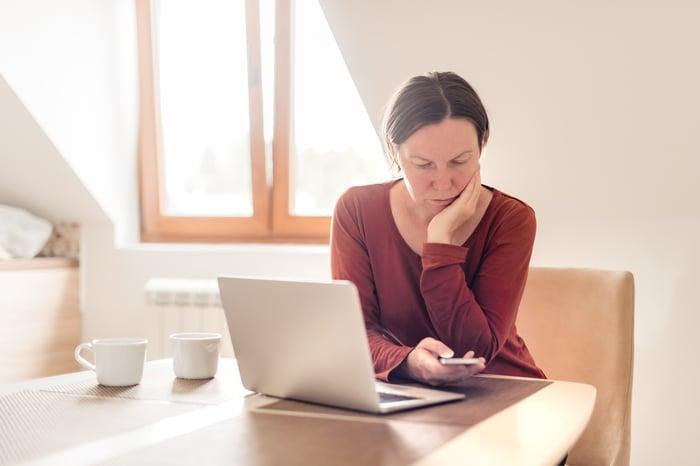 Woman at laptop looking down at phone