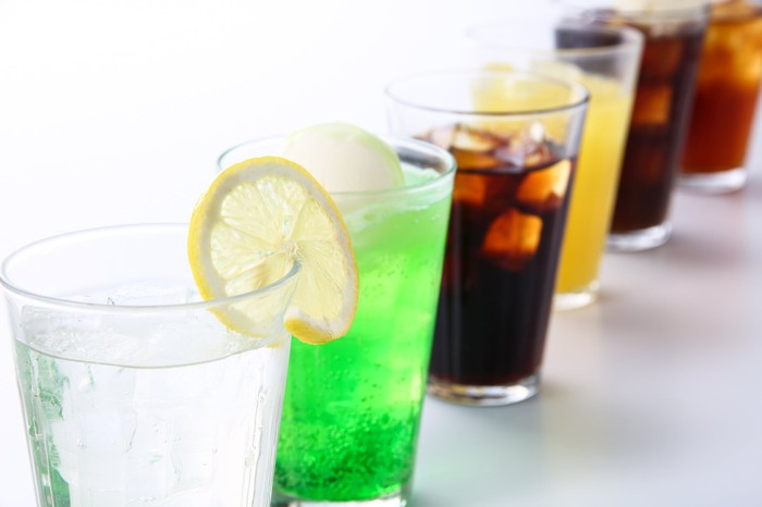Assorted soft drinks arranged in a row of transparent cups.