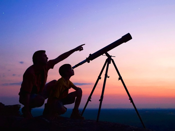 A father and son look through a telescope at sunset.