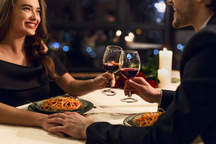A man and a woman clink glasses of red wine and hold hands across a table, with plates of pasta in front of them