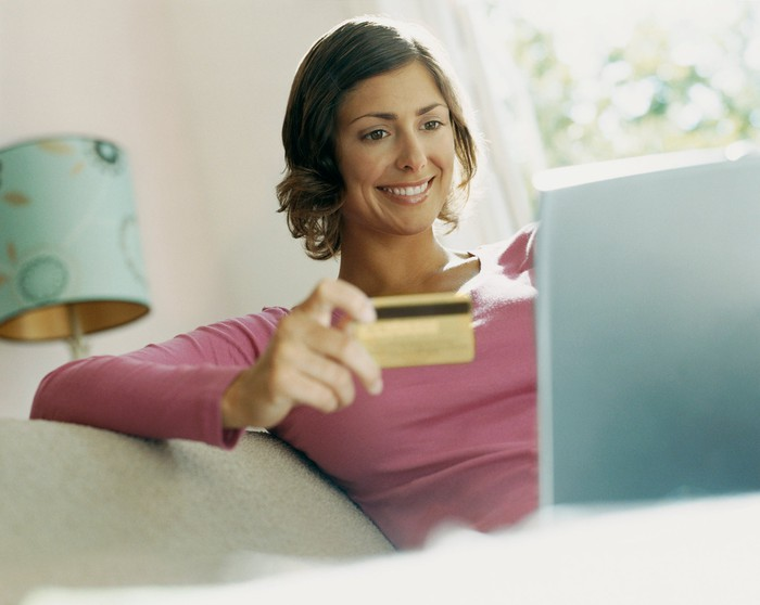 A woman looking at a laptop and smiling while holding a credit card