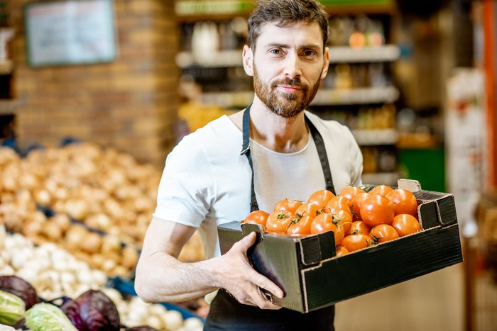 Man wearing apron in supermarket holding box of tomatoes