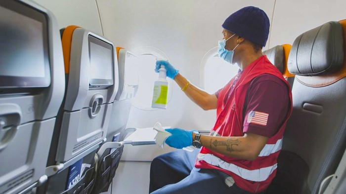 A JetBlue employee cleans an airplane interior.