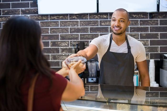 Man in apron handing food carton to woman