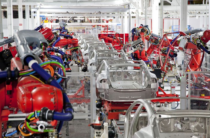 Robots tend to partially-assembled Teslas on an assembly line.