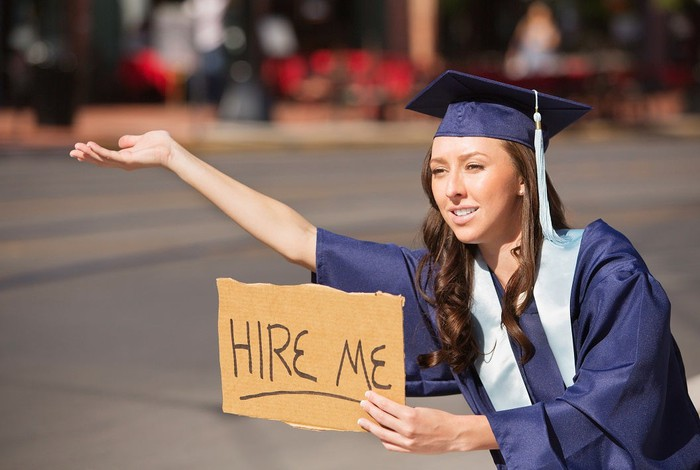A woman wearing a graduation gown and cap holds her hand out with a sign saying Hire Me.