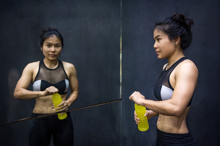 Woman taking a break from exercising in front of mirror.