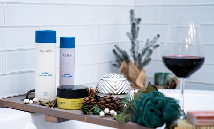 Nu Skin products on a tray over a bath, accompanied by a glass of wine.