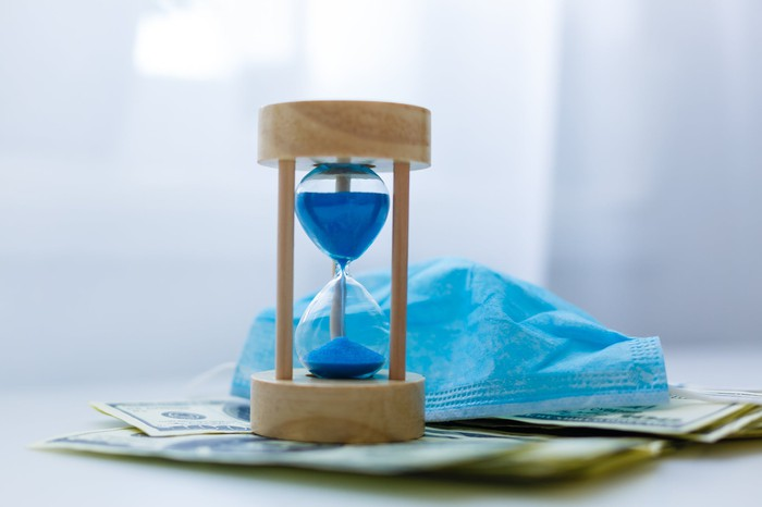 An hourglass on money.