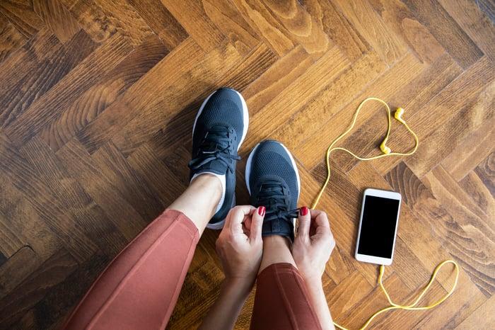 A woman tying her Nike shoes.