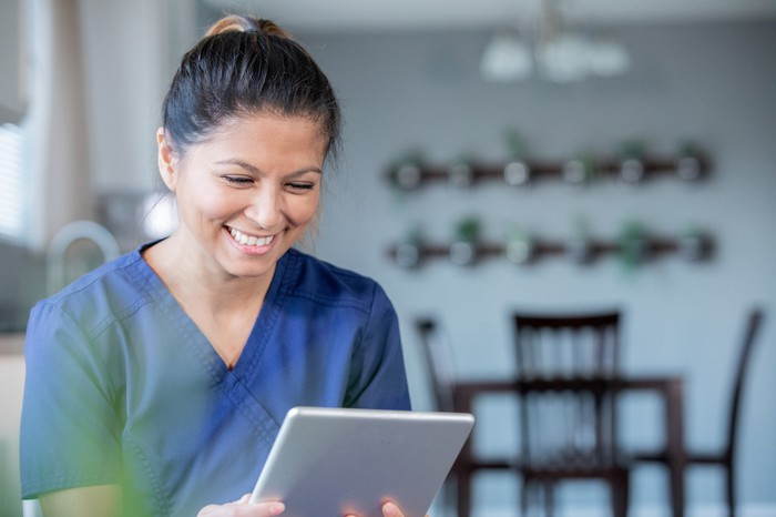 Smiling nurse holding a tablet on a virtual visit with a patient.