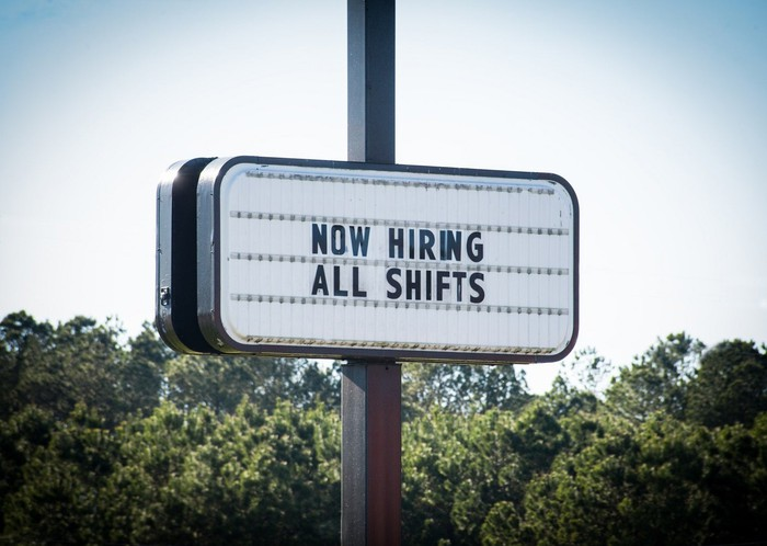 Sign reading now hiring all shifts.