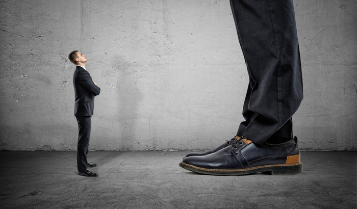 A small businessman looks upwards at a giant businessman whose shoes and pants are only seen in the frame.