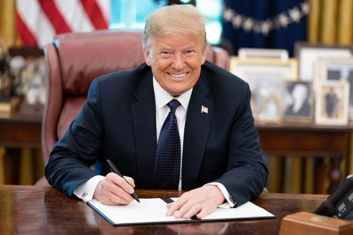 President Trump signing memorandum at his desk.