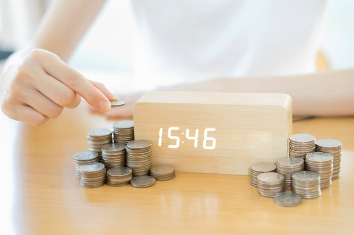 A woman is stacking coins in piles around a modern digital clock.