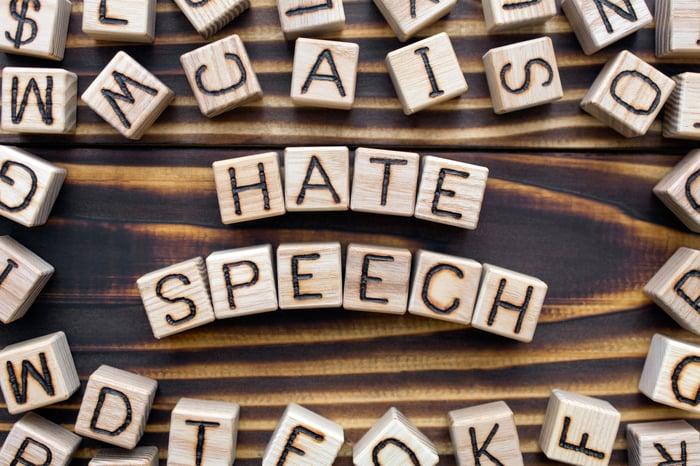"Letter blocks spelling ""Hate Speech"" on a table."