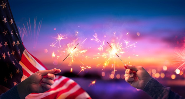 Hands holding sparklers in front of American flag background.