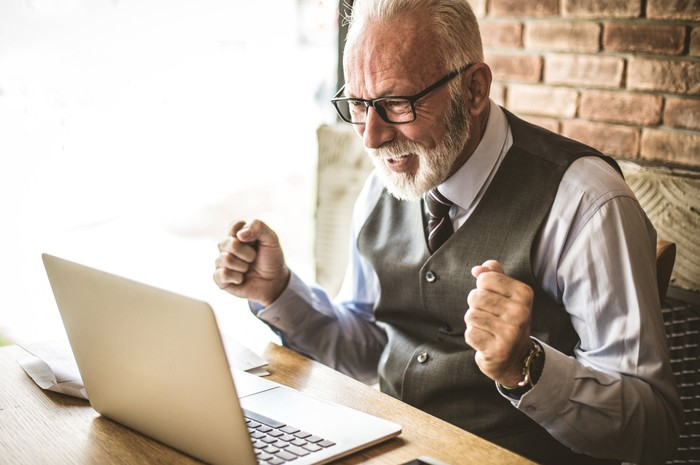Older man looking at laptop with happy expression.