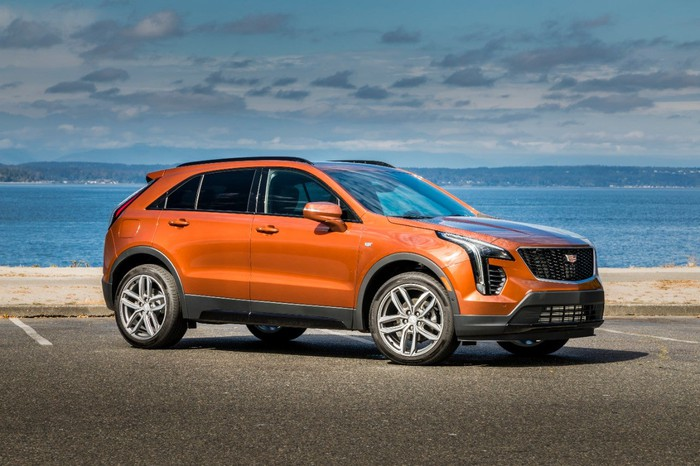 A parked orange Cadillac XT4, with a beach in the background