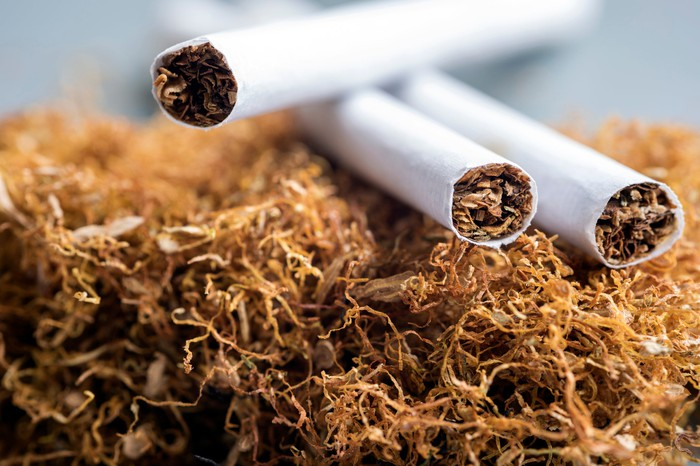 Three cigarettes on top of a pile of tobacco.