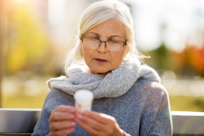 Older woman on bench looking at prescription bottle