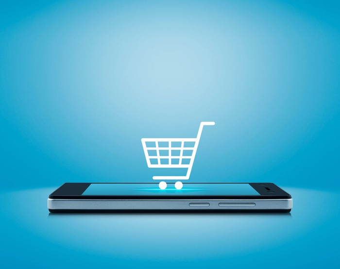 A shopping cart icon on top of a smartphone.