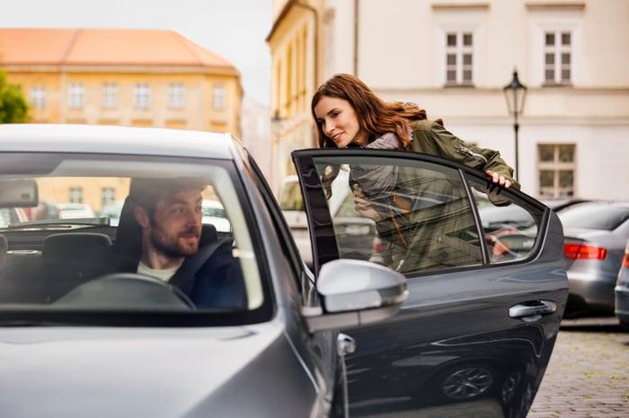An Uber driver picks up a female passenger.