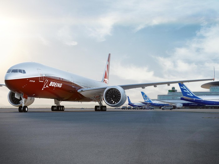 Red and white Boeing aircraft taxiing away from three blue and white Boeing aircraft parked at gates.