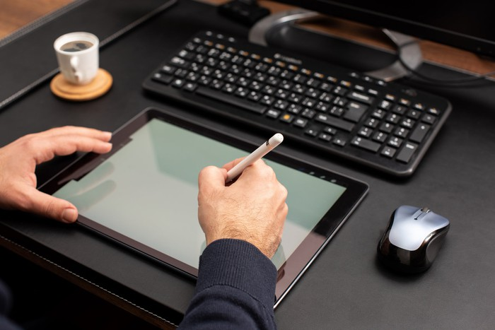 Person writing on tablet with stylus