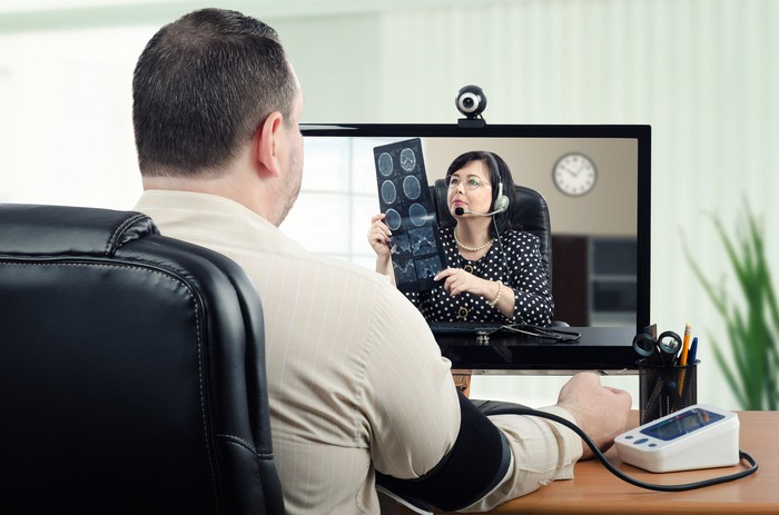 A man speaking with a doctor via a videoconferencing app on his computer.