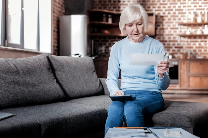 Older woman sitting on couch looking at check with calculator in hand.