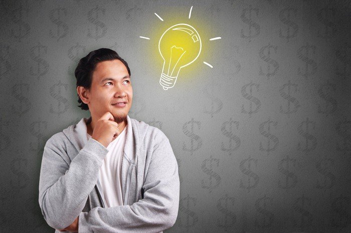 Young man with an image of a light bulb next to his head and dollar signs in the background