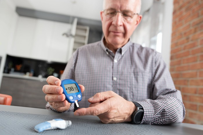 An elderly man using a glucometer to control his blood sugar levels.