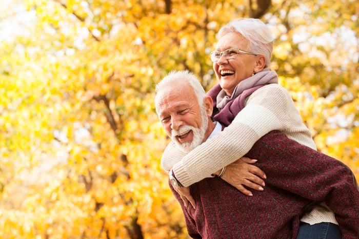 Smiling older man holding smiling older woman on his back