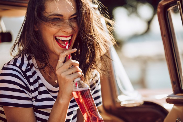 Woman drinking a reddish soda out of a glass bottle via a striped straw