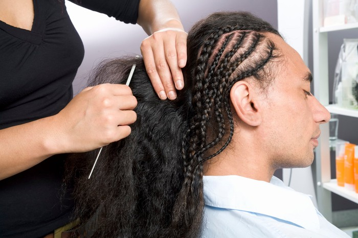 Woman styling a man's hair in multiple braids at a salon.