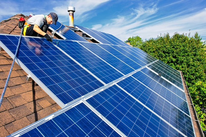 A technician installs solar panels on a residential roof.