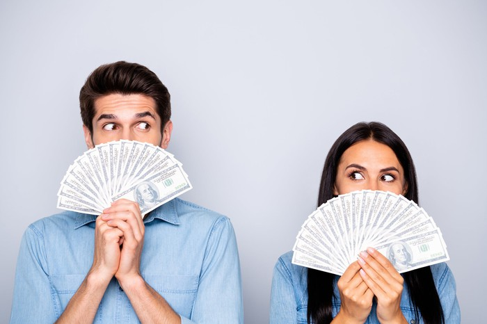 A man and a woman holding open fans of hundred-dollar bills over their faces.