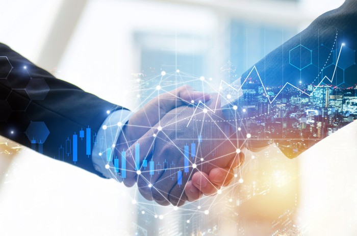 Two people shaking hands behind a network image.